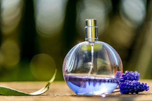 Frasco de perfume, uma flor azul no lado com bokeh de fundo. copyspace para texto.
