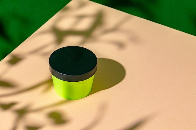 Frasco de plástico verde para produtos para a pele em superfície bege com sombra