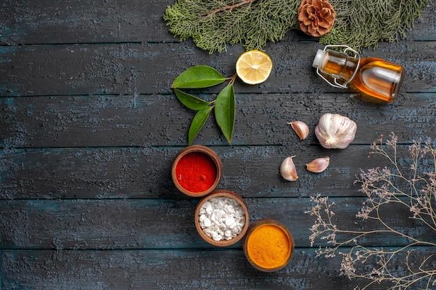 Frasco de prato de natal de vista superior com tigelas de óleo de especiarias, limão e alho ramos de abeto com cones na mesa escura