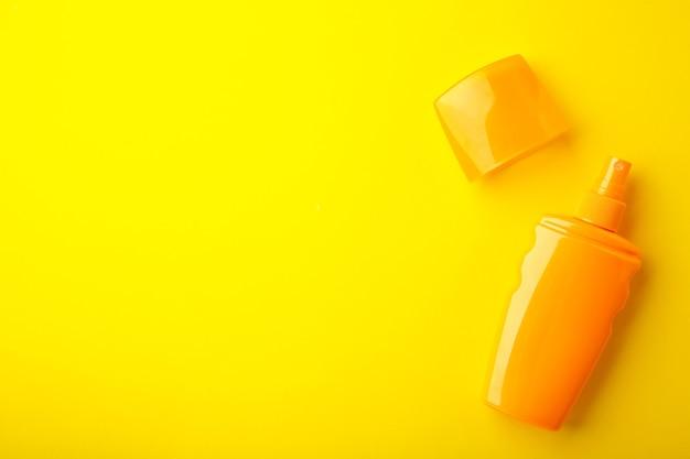 Frasco de proteção solar em fundo amarelo. férias de verão. vista do topo.