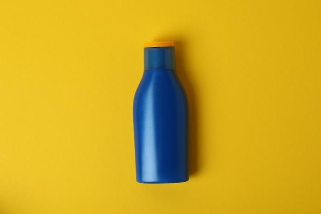 Frasco de protetor solar azul em fundo amarelo isolado