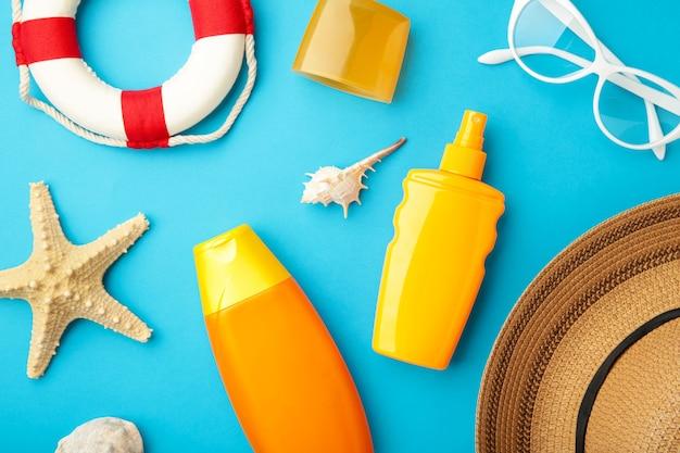 Frasco de protetor solar com chapéu, óculos e outros acessórios em fundo azul.