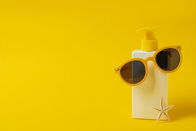 Frasco de protetor solar com óculos de sol e estrelas do mar em fundo amarelo isolado