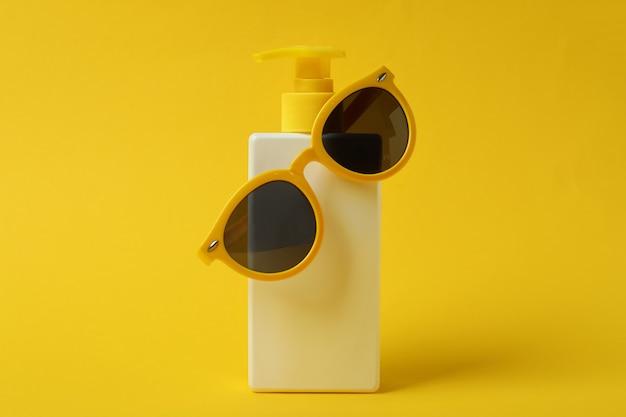 Frasco de protetor solar com óculos de sol em fundo amarelo isolado