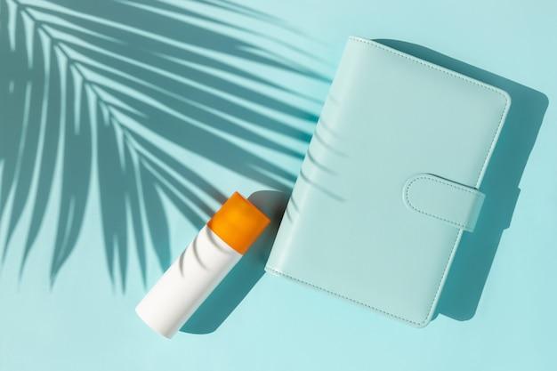 Frasco de protetor solar e bloco de notas com sombra de folha de palmeira na superfície azul