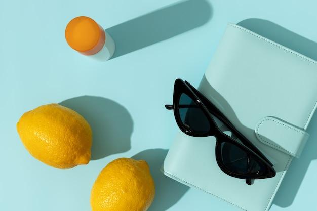 Frasco de protetor solar e bloco de notas com sombras profundas na superfície azul