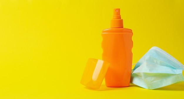 Frasco de protetor solar e máscara médica em fundo amarelo isolado