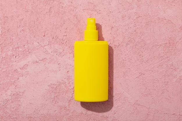 Frasco de protetor solar em branco na superfície rosa