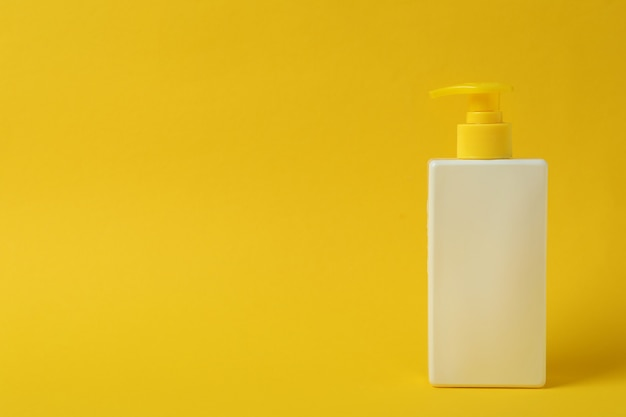 Frasco de protetor solar em fundo amarelo isolado