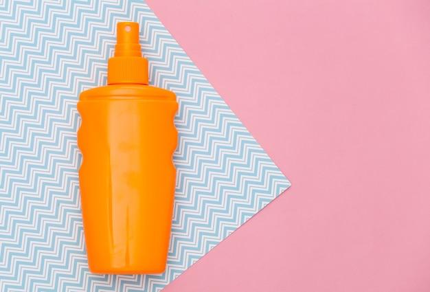 Frasco de protetor solar em pastel azul rosa. proteção da pele. férias na praia