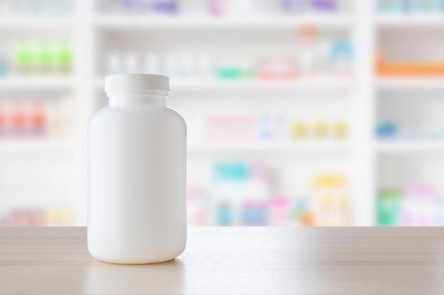 Frasco de remédio branco no balcão de madeira com prateleiras de farmácias desfocam o fundo farmacêutico