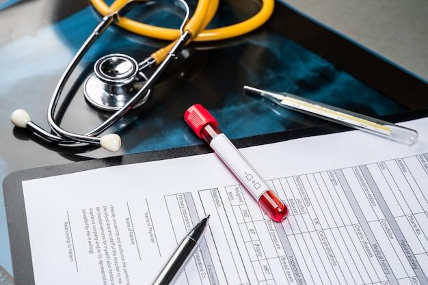 Frasco de sangue com amostra de sangue no formulário de teste