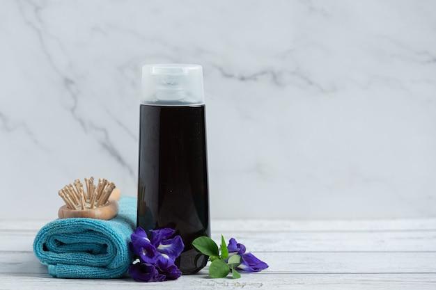 Frasco de shampoo de flor de ervilha borboleta colocado sobre fundo branco de madeira