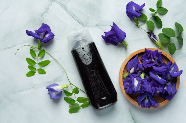 Frasco de shampoo de flor de ervilha borboleta colocado sobre fundo de mármore branco