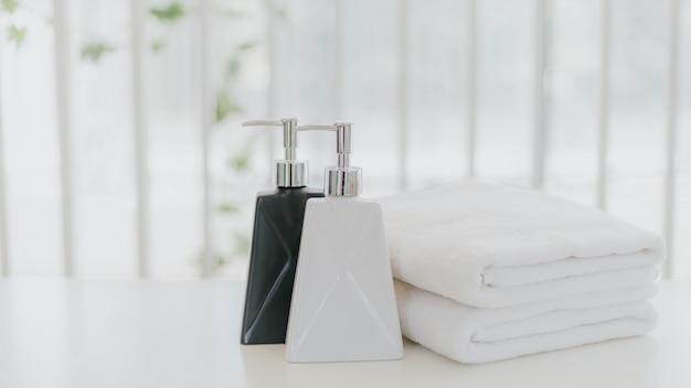 Frasco de shampoo e creme de banho com toalha