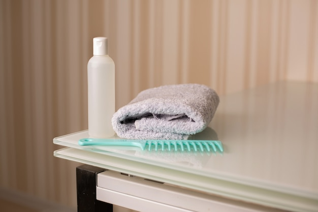 Frasco de shampoo natural e pente com toalha de banho em uma mesa sobre fundo bege neutro. espaço para texto