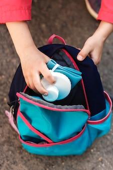 Frasco de silicone dobrável na mão da menina colocando-o na mochila