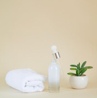 Frasco de soro cosmético de vidro transparente em branco próximo à planta e toalha