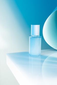 Frasco de soro cosmético em uma mesa branca, luz de néon azul, maquete