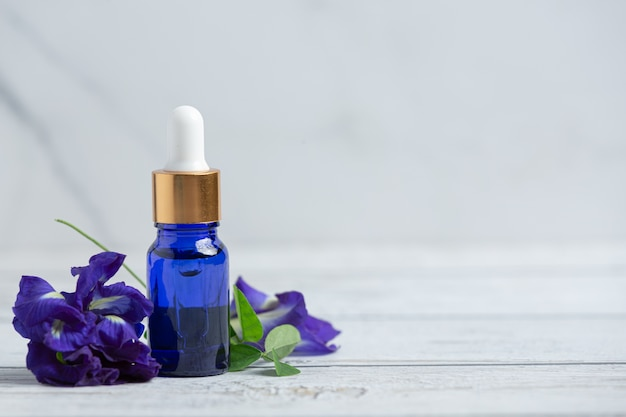 Frasco de soro de óleo de flor de ervilha borboleta colocado no chão de madeira branco