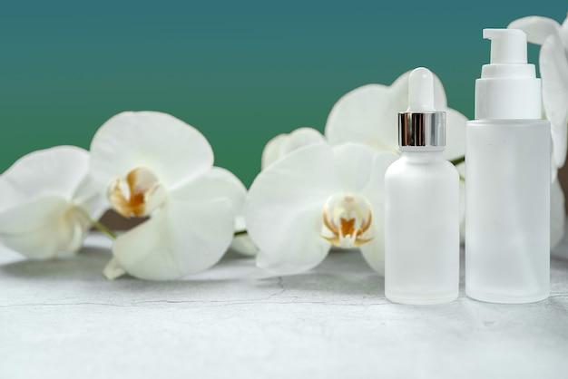 Frasco de soro de vidro branco, frasco de bomba de loção e maquetes de frasco de creme no banheiro com flores de orquídea ao fundo, produtos cosméticos sem marca, maquete de marca de produto cosmético de spa