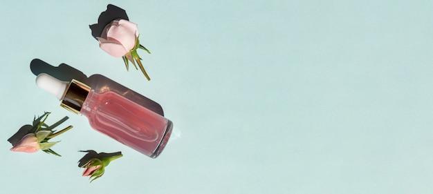 Frasco de soro de vidro transparente com água essencial rosa sobre fundo azul. produto de beleza da moda para pele jovem. etapa adicional de hidratação na rotina facial do dia a dia. bandeira