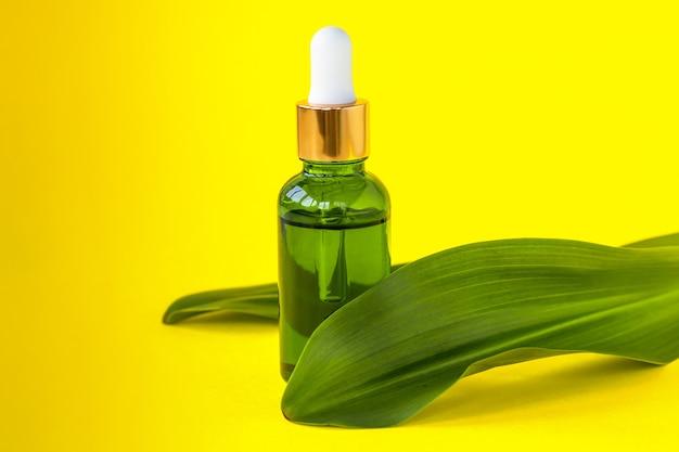 Frasco de soro na folha verde. produto de beleza da moda para pele jovem. etapa adicional de hidratação na rotina facial diária.