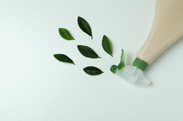 Frasco de spray de detergente em branco e folhas em fundo branco isolado