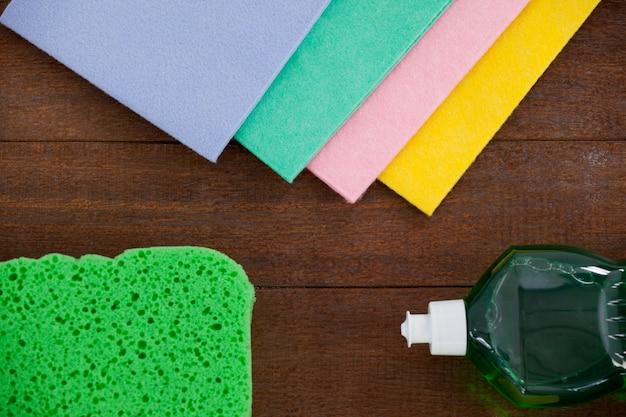 Frasco de spray detergente e várias esponjas de limpeza