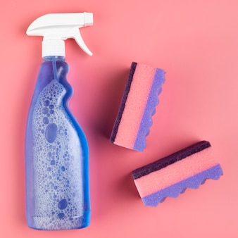 Frasco de spray plana leigos e esponjas em fundo rosa