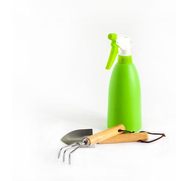 Frasco de spray verde e ferramentas de jardim em fundo branco. conceito de cuidados com a planta