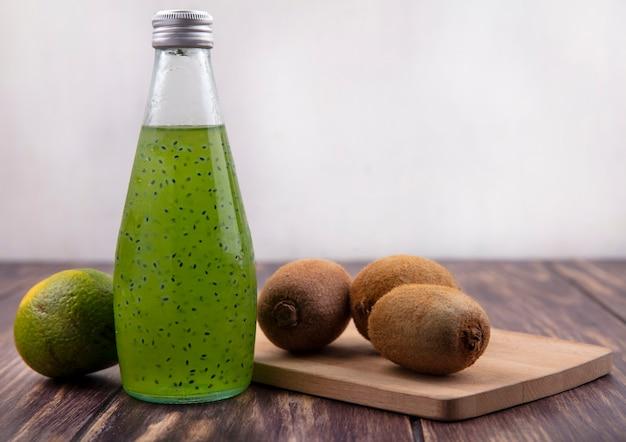 Frasco de suco com tangerina verde e kiwi em uma tábua