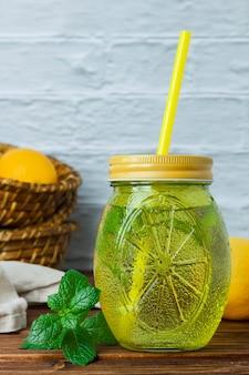 Frasco de suco de limão com folhas, pano branco, limões na vista lateral da caixa de madeira em uma superfície de madeira