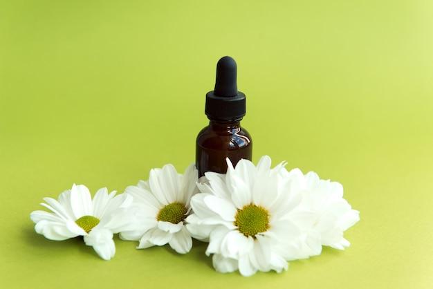 Frasco de tratamento de pele com flores sobre fundo verde cosmético ou produto de saúde