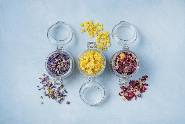 Frasco de três com chá de ervas aromáticas lavanda, rosa e camomila a granel na mesa de madeira azul