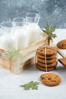 Frasco de três copos de leite com biscoitos de chocolate.