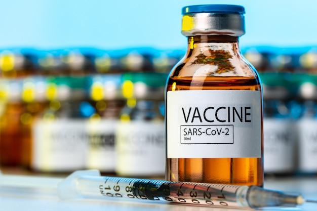 Frasco de vacina covid-19 com uma seringa na mesa do laboratório