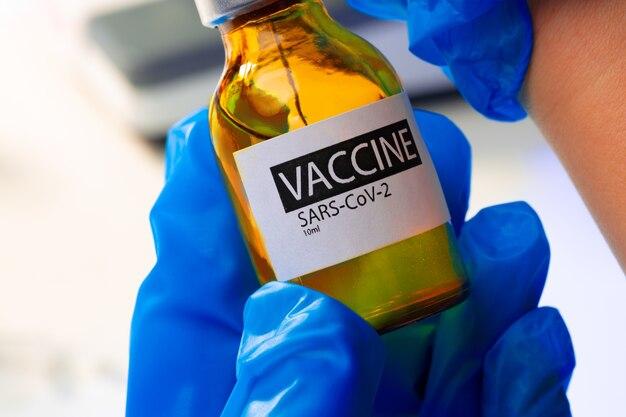 Frasco de vacina covid-19 com uma seringa retirando a vacina de perto