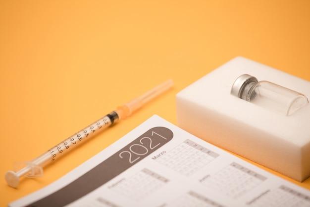 Frasco de vacina em blister, com calendário 2021 e seringa, superfície laranja
