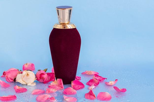 Frasco de veludo com perfume feminino. cercado por pétalas de rosa em um espaço claro.