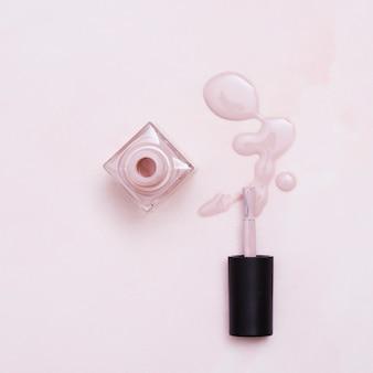 Frasco de verniz de unha derramado com pincel em fundo rosa