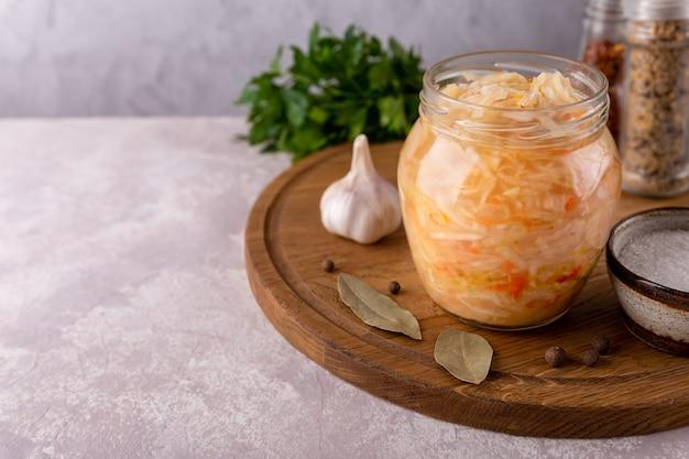 Frasco de vidro aberto de chucrute de salada caseira na tábua redonda close-up com folha de louro picante, alho, sal, salsa no espaço da cópia de fundo cinza. comida fermentada e saudável.