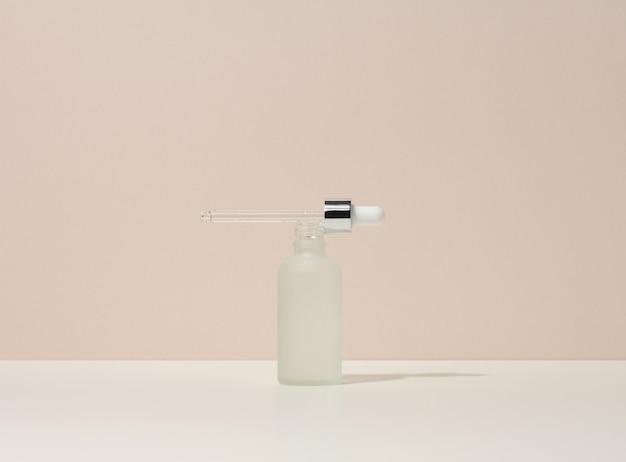 Frasco de vidro branco com pipeta fica em um fundo bege. branding de cosméticos spa. embalagem para gel, soro, publicidade e promoção de produto, mock up