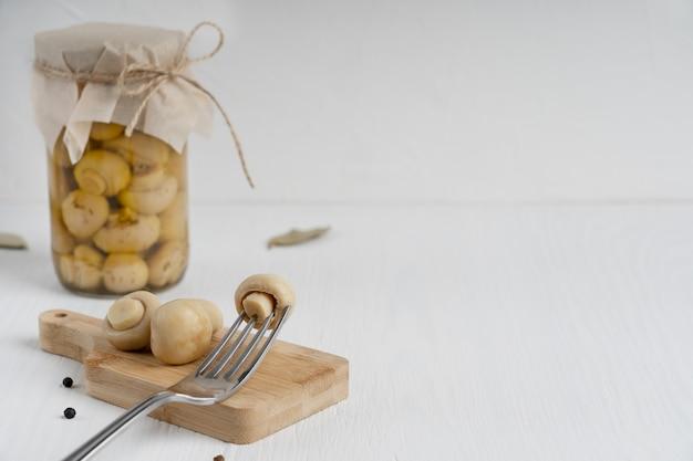 Frasco de vidro cheio de cogumelos champignon em conserva servidos na tábua com um garfo na mesa de madeira
