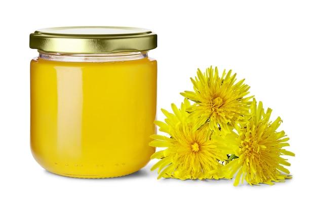 Frasco de vidro cheio de doce mel floral e flores de dente de leão quase isoladas no fundo branco
