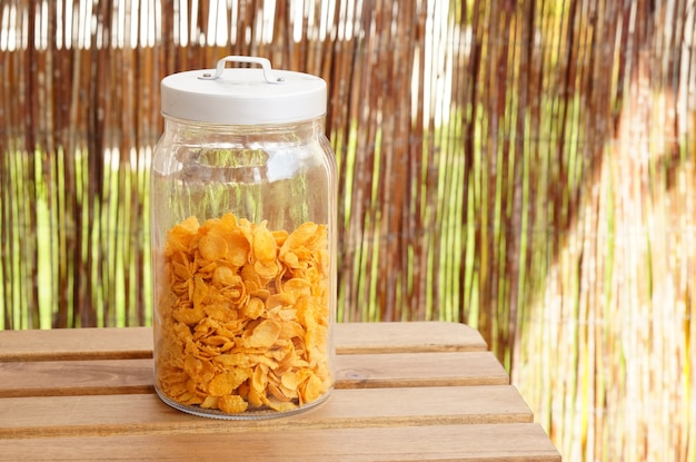 Frasco de vidro cheio de flocos de milho em uma mesa de madeira