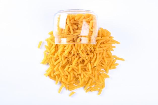 Frasco de vidro cheio de macarrão amarelo seco rotini isolado