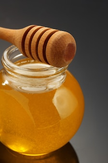 Frasco de vidro cheio de mel e pau em fundo preto