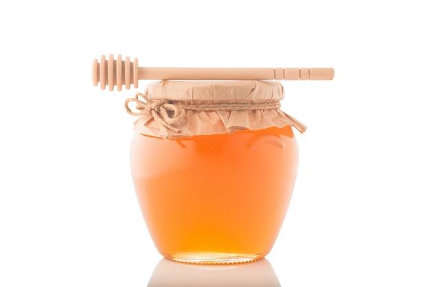 Frasco de vidro cheio de mel e vara de madeira nele isolado em um fundo branco