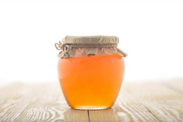 Frasco de vidro cheio de mel e vara de madeira nele isolado em um fundo de madeira